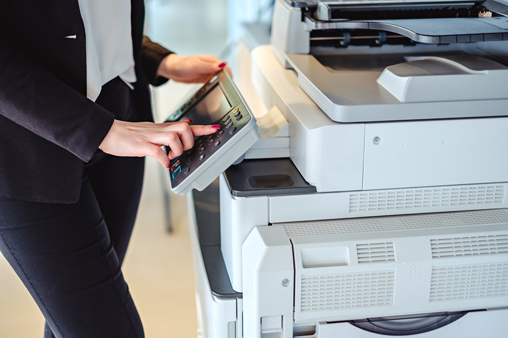 woman using multi-function printer in office