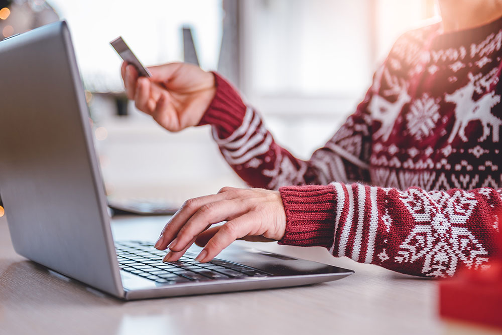 Person wearing a festive sweater uses a laptop